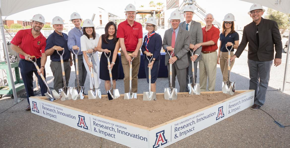 A group of a dozen people wearing white construction hats hold shovels that are placed into a square of dirt.