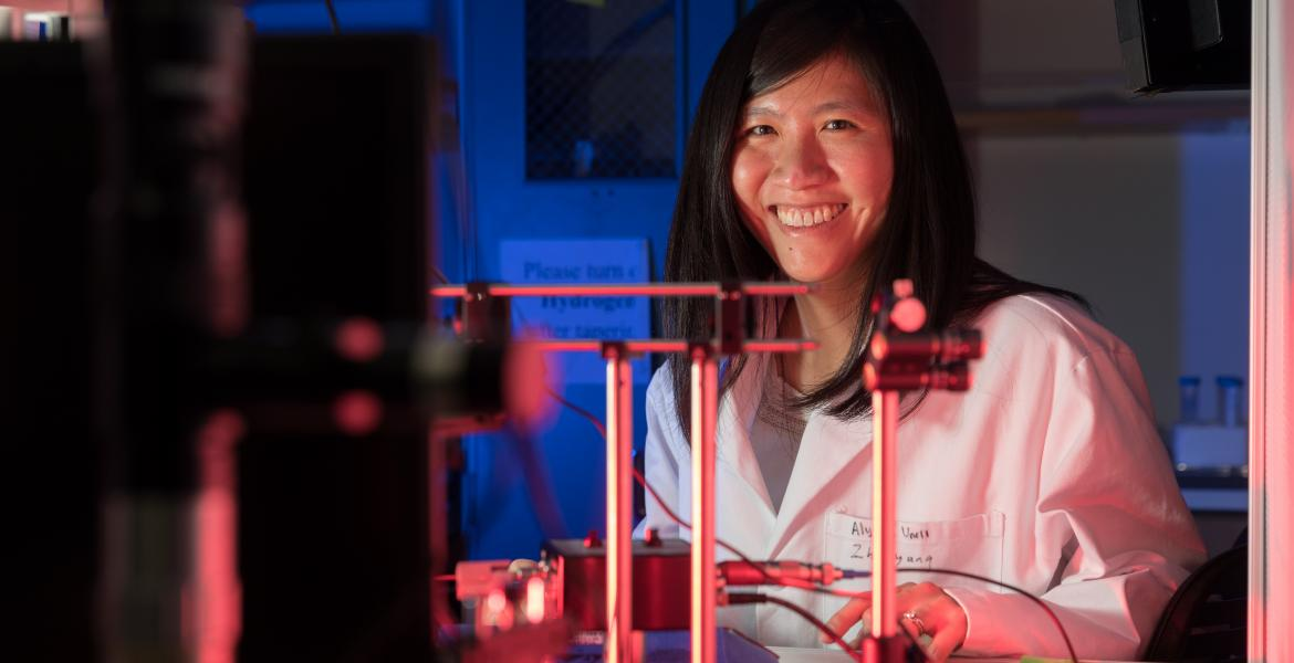 Judith Su wearing a white labcoat and smiling behind a complicated array of sensors.