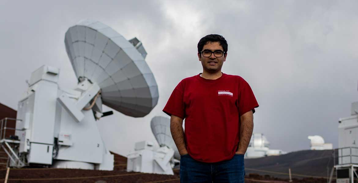 Arash Roshanineshat stands in front of a big, white satellite on a cloudy day.