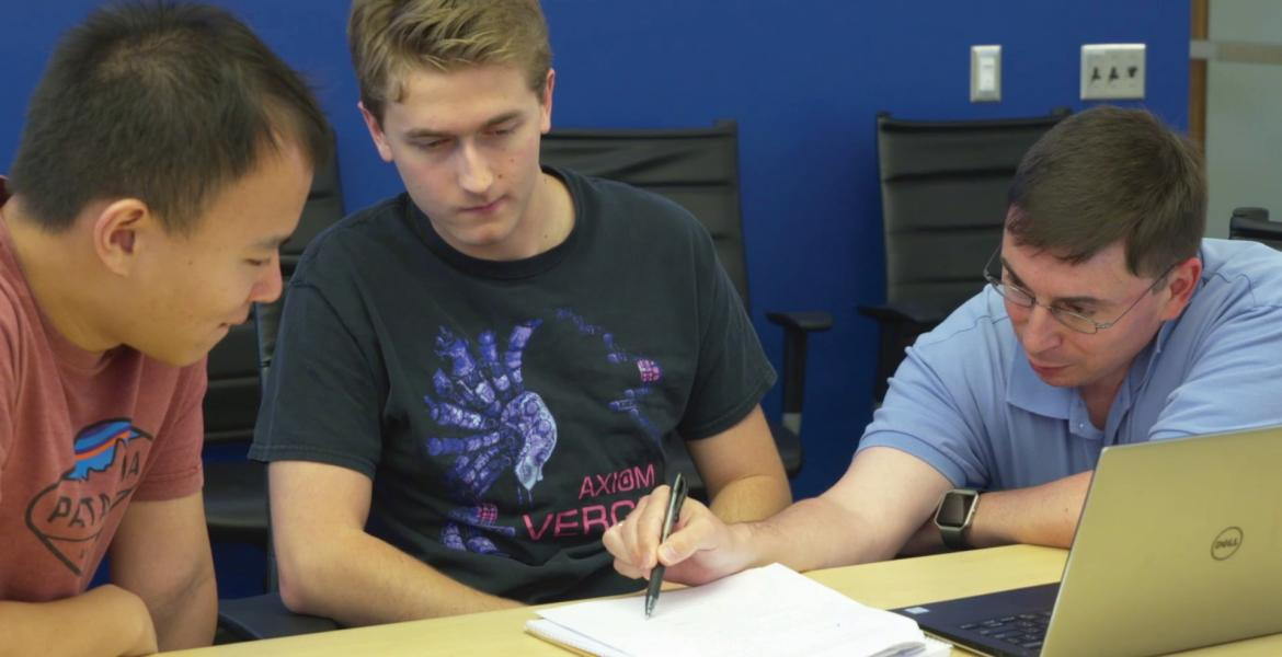 Three men lean over a sheet of paper and a laptop, the one on the far right pointing and explaining a concept.