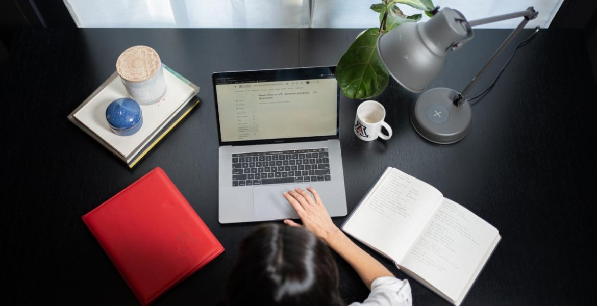A photo of a woman at a desk, taken from overhead. the desk has a laptop, an open notebook, a stack of folders, a plant, a lamp and a University of Arizona coffee mug.