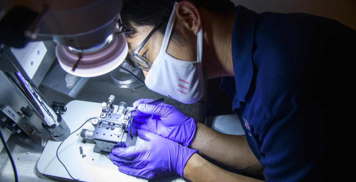 Dongkyun Kang, wearing rubber gloves and a mask, leans over to work on a small device under a bright light.