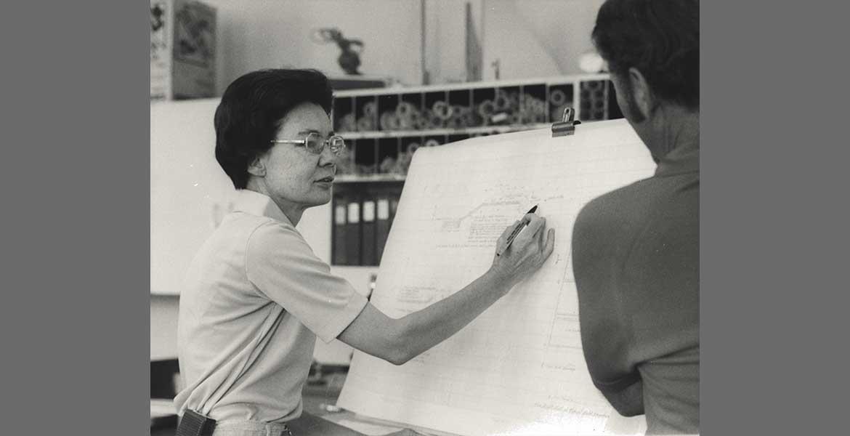 Frances Walker explaining a blueprint on a large white sheet of paper to an onlooker.