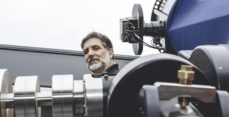 Roberto Furfaro standing behind a telescope