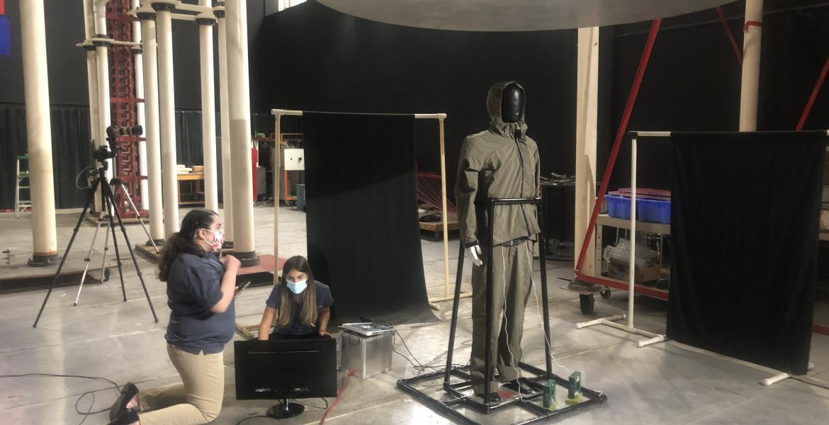 A mannequin covered in black tape is held up by a PVC pipe frame in a large room. Two students kneel next to electronic equipment near the mannequin.