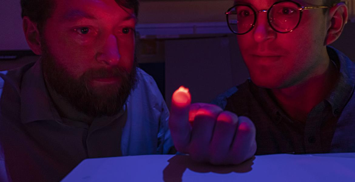 Two men, visible from the shoulders up, in a dimly lit room. The man on the left is holding a small, reddish light source on his hand, which is illuminating their faces. Both are staring at the light.