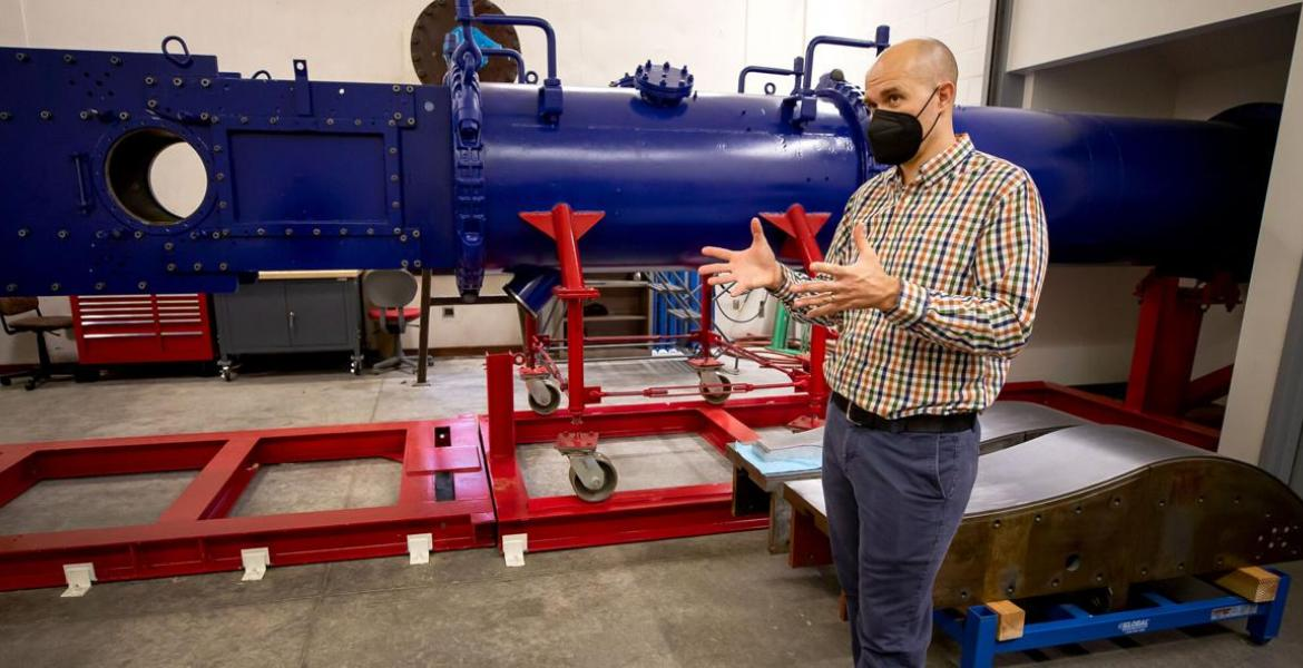 Jesse Little stands in front of a large blue wind tunnel -- it looks like a horizontal pipe -- on red scaffolding. He is wearing a black mask over his nose and mouth and gesturing with his hands to explain something.