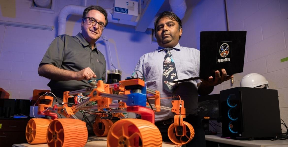 In the foreground, a robot with four orange wheels. Two men stand behind the robot.