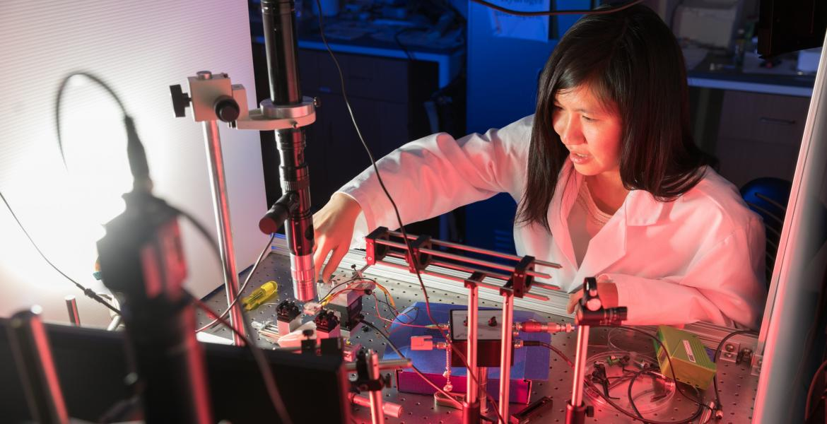 Judith Su wearing a white labcoat and leaned over a complicated array of sensors.