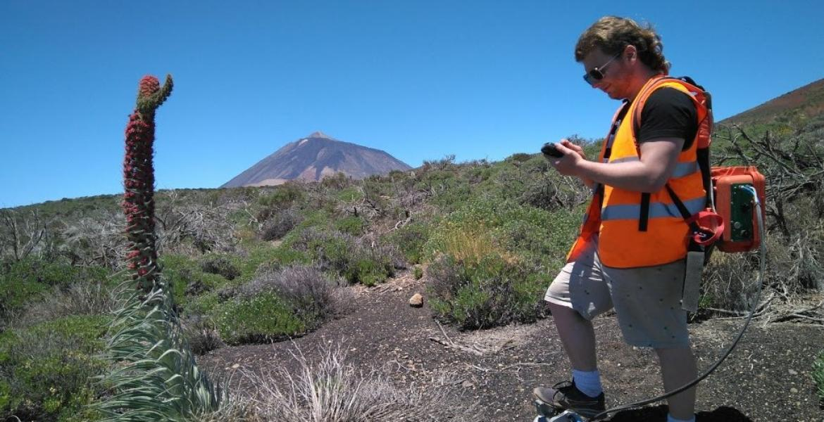 A young man in an orange vests stands in an area with volcanic rock.