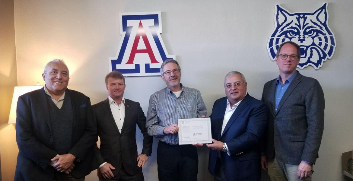 Five men stand in front of a wall with a University of Arizona block A and wildcat logo on it.