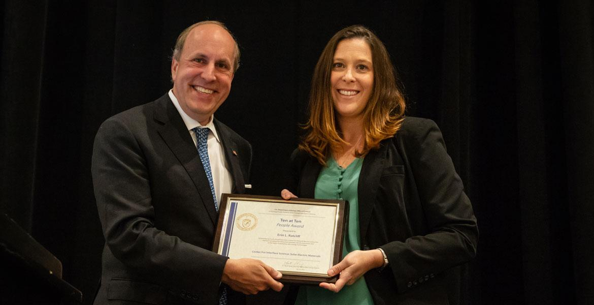 Erin Ratcliff receives a framed certificate from Department of Energy Under Secretary for Science Paul Dabber