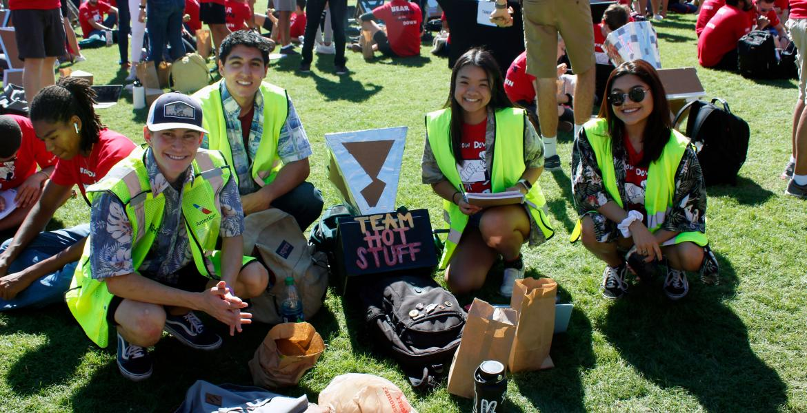 Two young men and two young women wearing Hawaiian shirts and bright yellow vests kneel for a photo next to their solar oven, a cardboard and aluminum foil device labeled with their group name: