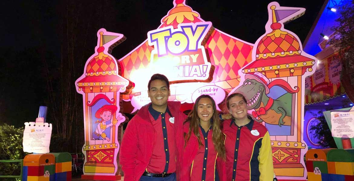 Three smiling people in Disney uniforms in front of the Toy Story Mania! attraction.