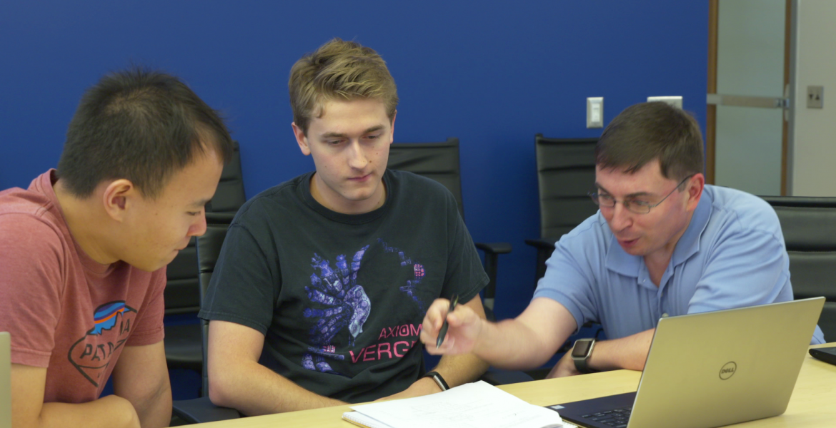 Three men lean over a laptop and set of papers on a table.