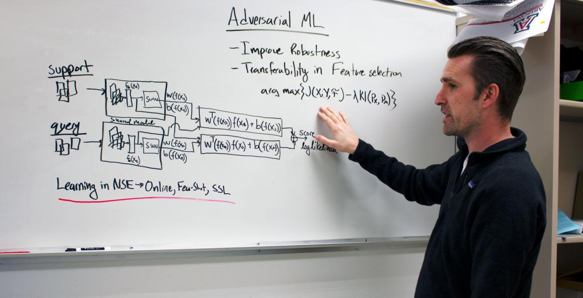 Gregory Ditzler explains a concept at a whiteboard.