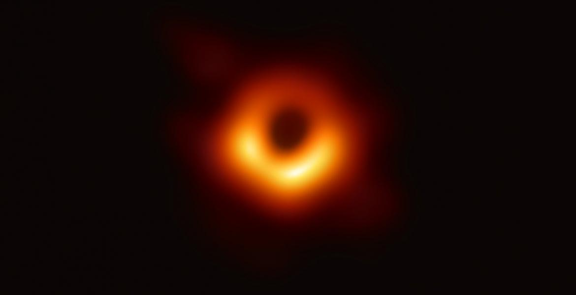 Photo of a black hole -- it looks like an orange ring surrounded by blackness