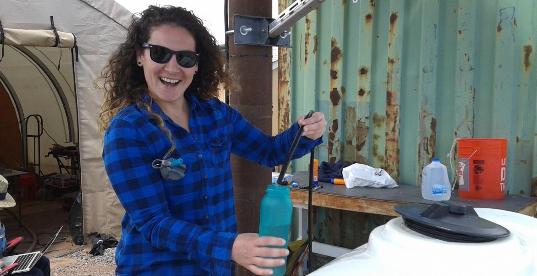 Vicky Karanikola smiling, wearing sunglasses and holding a water bottle.