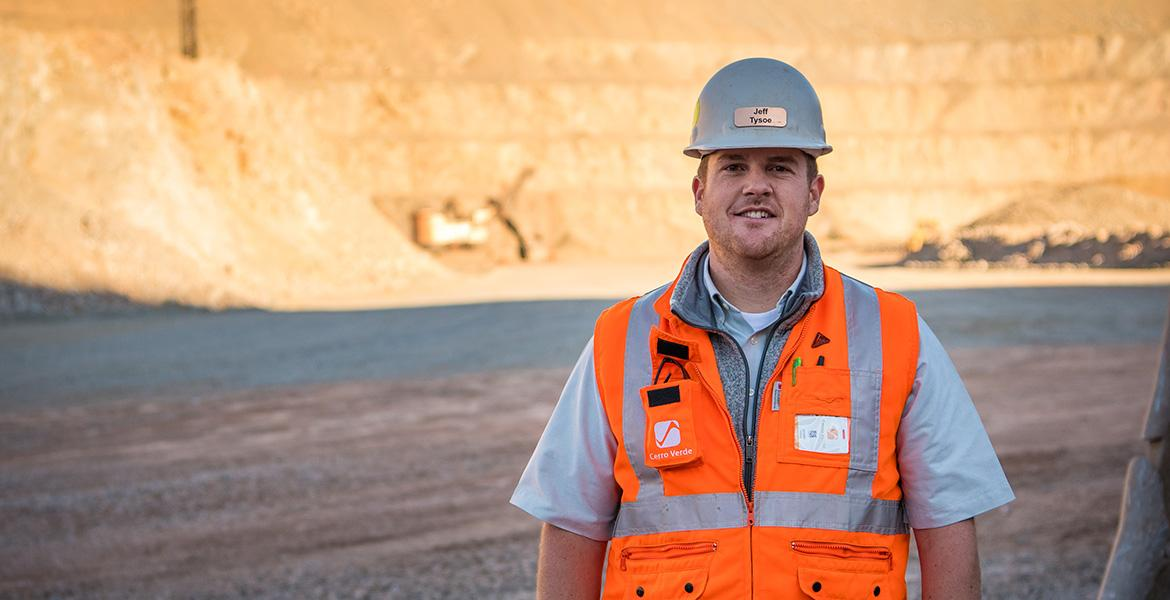 UA mining engineering alumnus Jeff Tysoe stands at the bottom of an open pit mine in a hardhat and orange safety vest