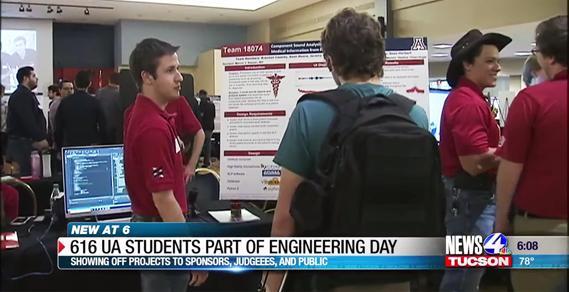 A student in a red polo stands in front of a scientific poster talking to someone in a green shirt reading the poster.