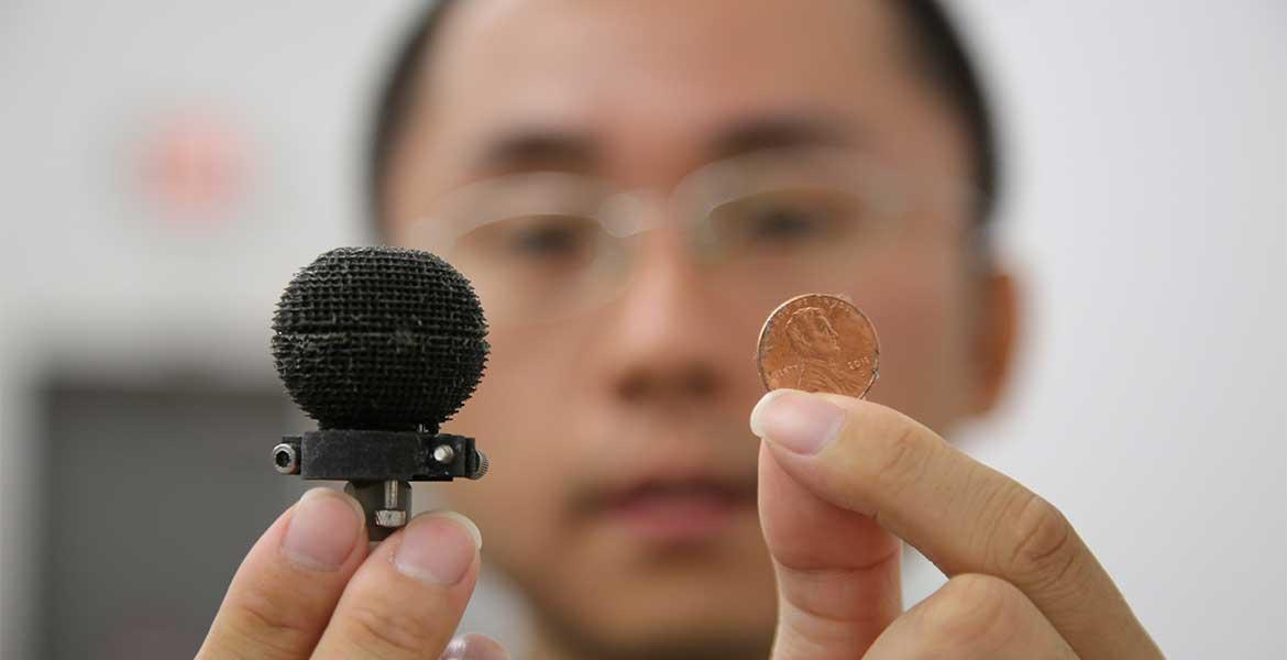 A man holds up a small 3D-printed black sphere in one hand, a penny in the other. The sphere is only about 3 times the size of the penny.