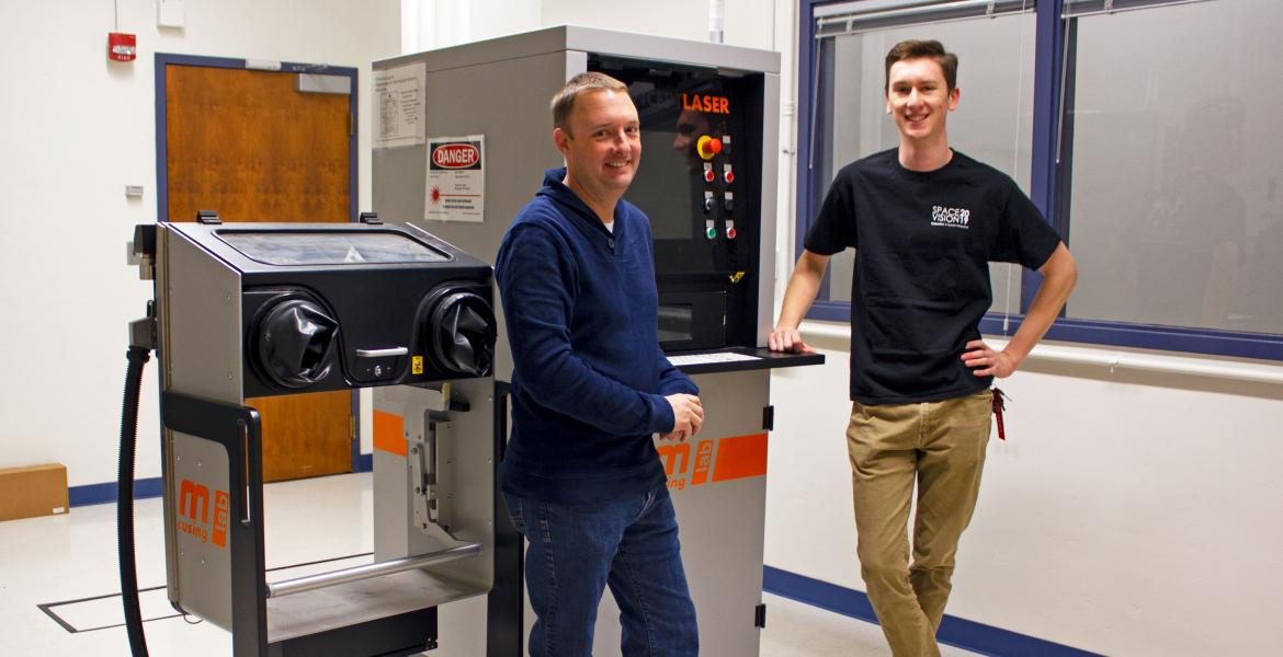 Two young men standing next to a machine about the same height as them, with a screen and a series of buttons. It says