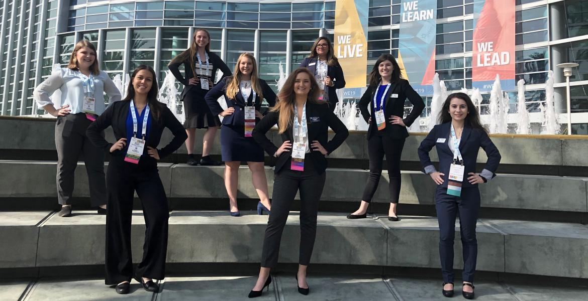 Eight women in professional attire stand on three levels of steps posing for a photo in front of the Anaheim Convention Center.