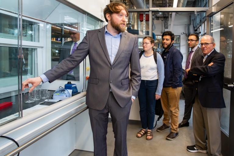 Biomedical engineering assistant professor Philipp Gutruf shows a group some of the lab's equipment.