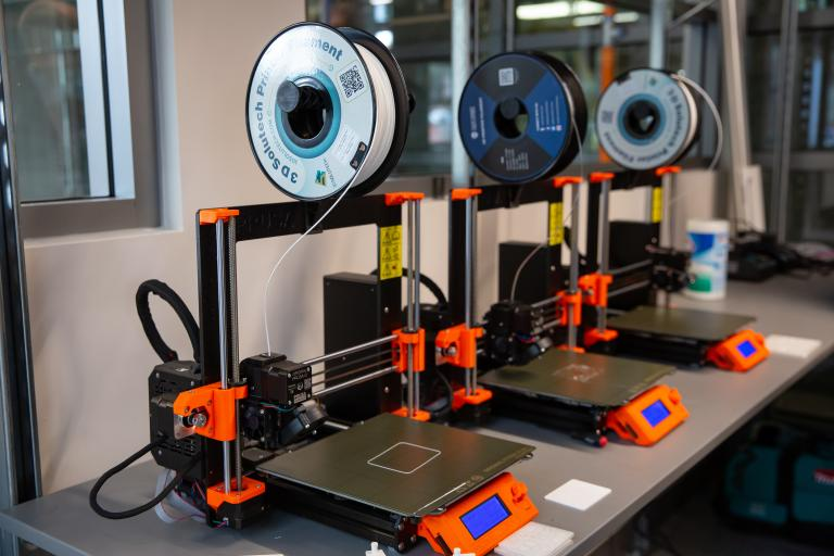 A row of 3D printers in the new lab.