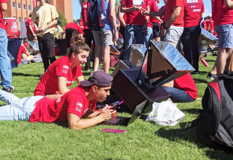 A student checks the rising temperature of his team's solar oven.