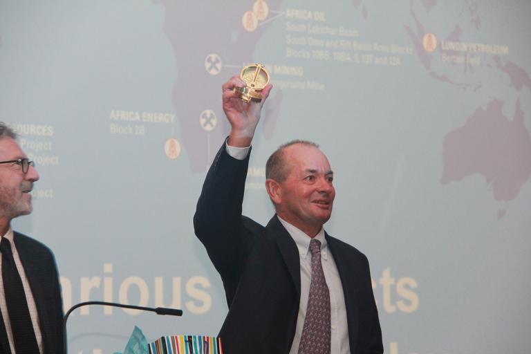 Lukas H. Lundin lifts his commemorative compass after delivering the 2016 Lacy Lecture for the Department of Mining and Geological Engineering