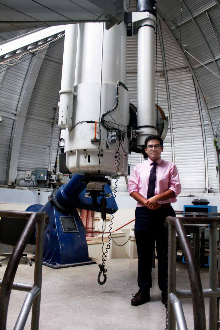 Arash Roshanineshat in front of the Steward Observatory's enormous telescope.