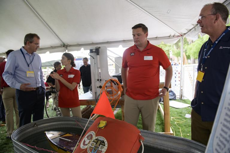 Future Dean David Hahn, interim Dean Larry Head and two students stand around a large metal basin of water with a flotation device and an orange flag in it.