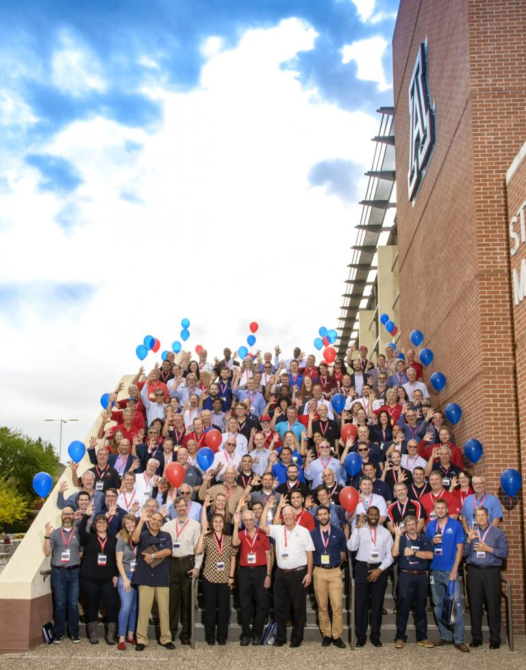 About 120 people pose for a photo on a large staircase outside the UA Student Union, flanked by red and blue balloons, and against a backdrop of a beautiful cloudy sky.