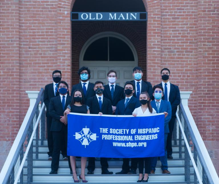 """A group of students stands on the front steps of Old Main, wearing face masks and holding up a blue banner that reads """"Society of Hispanic Professional Engineers. www.shpe.org."""""""