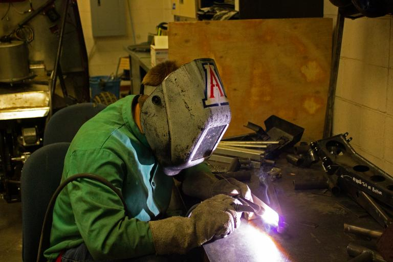 A person wearing a welding helmet and leaned over a welding gun
