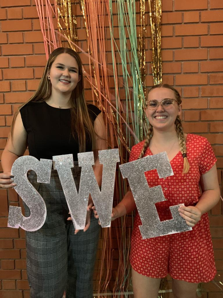 """Two smiling women holding up cardboard cutouts of the letters """"S W E"""""""
