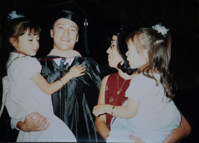 A man in a graduation cap and gown holds a young girl. Next to him is a woman in a red top holding another young girl.