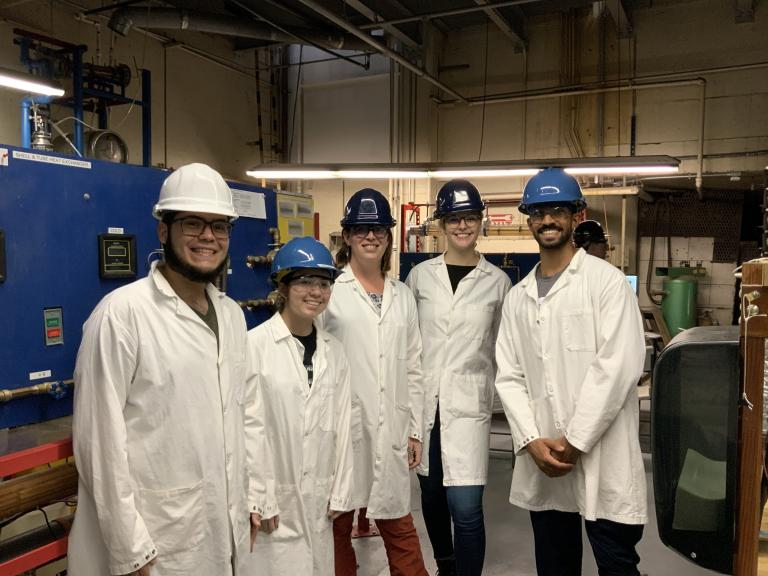 Five students in hard hats and lab coats.