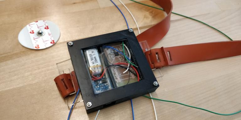 A small black square with a circuit board attached and a brown leather strap attached to it, similar to a watch strap.