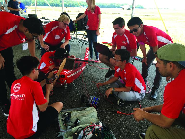A group of students in red shirts huddle around an airplane, which is about 6 feet long.