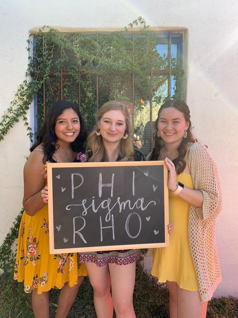 """Three smiling women hold a blackboard with the words """"Phi Sigma Rho"""""""