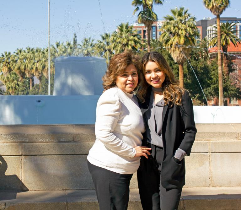 Jocelyne Rivera and her mother standing in front of a fountain.