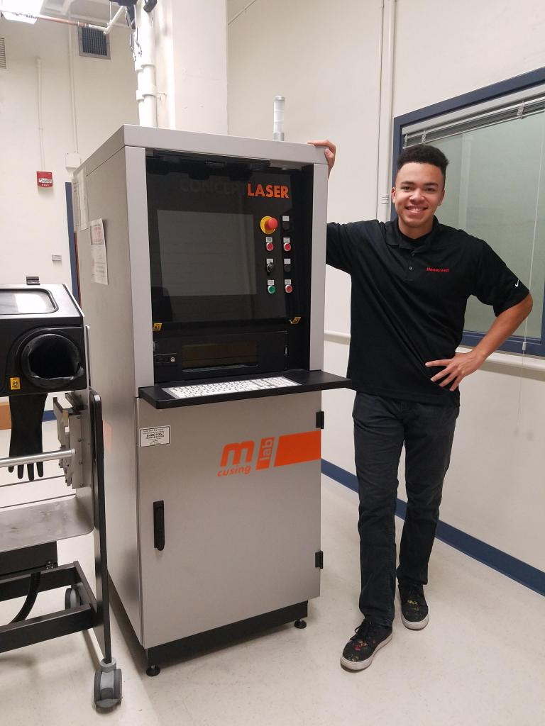 A man stands next to a 3D printing machine and smiles.