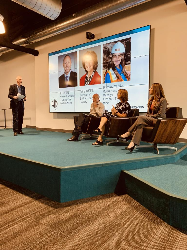 Three people sit in chairs on a stage, with a powerpoint with their photos behind them. One man stands and asks them questions.