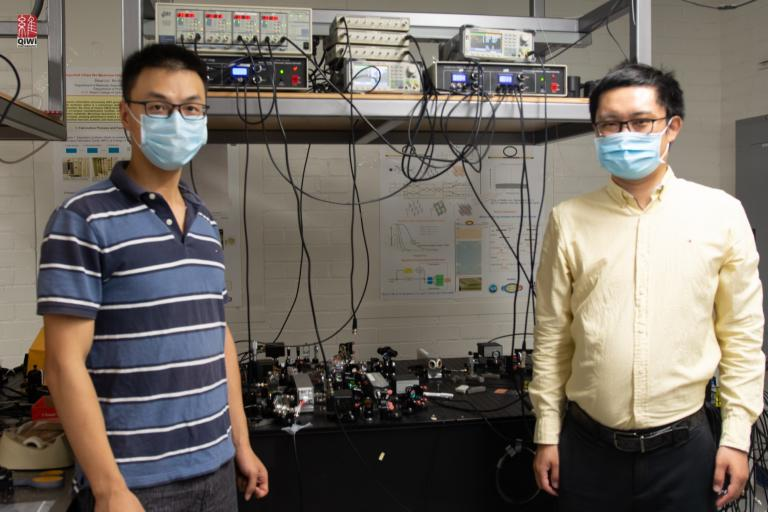 Quntao Zhuang and Zheshen Zhang, standing in a lab and wearing masks.