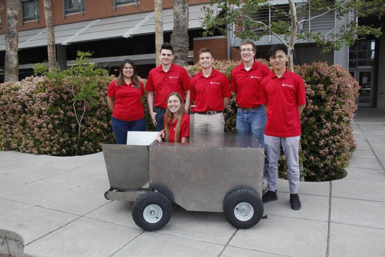 Five students stand around a big metal box on wheels. A sixth is sitting inside the box.