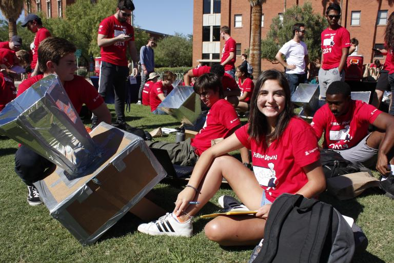 A young woman sits next to a solar oven and smiles.