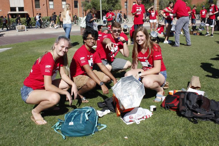 Four students in matching red shirts squat and pose next to a solar oven, a cardboard device about a foot across with a foil funnel-like structure on top.