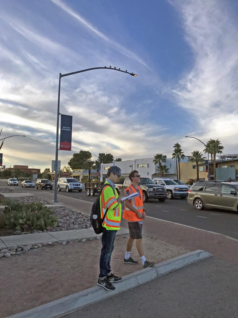 Two students wearing bright orange and yellow vests stand at an intersection along Speedway as the sun sets behind them.